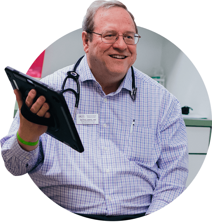 Image: Smiling Dr. Davis holding tablet with medical records.